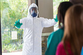 Doctor in hazmat suit stopping nurses from entering contaminated room