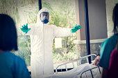 Doctor in hazmat suit warning nurses near infected patient