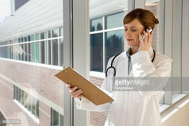 Arzt im Krankenhaus Blick in die Zwischenablage am Telefon