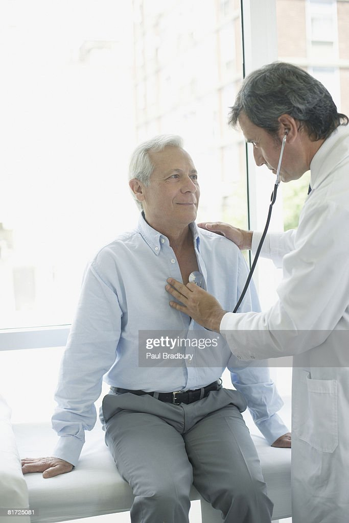 Doctor in hospital room with patient using stethoscope : Stock Photo