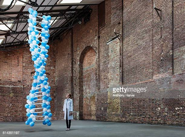 Doctor in warehouse with DNA made of balloons