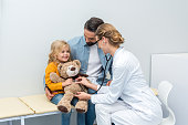 female doctor listening to breath of teddy bear of little girl