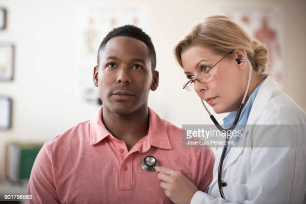 Doctor listening to heartbeat of patient in clinic
