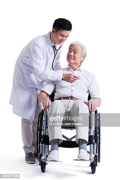 Doctor listening to wheelchair bound patient's heart