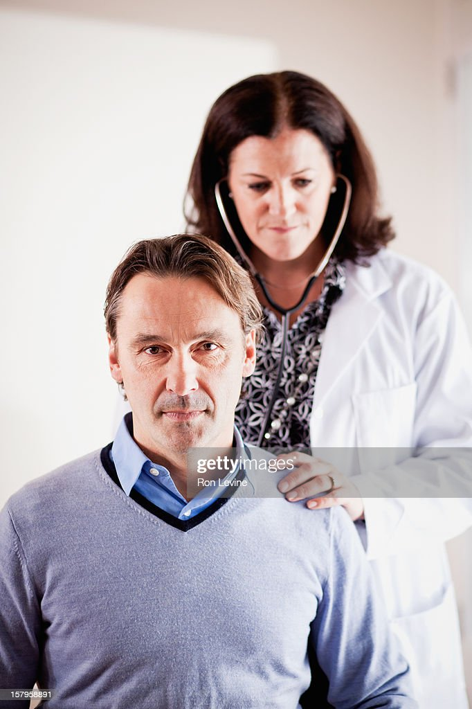 Doctor listens to patient's lungs with stethoscope : Stock Photo