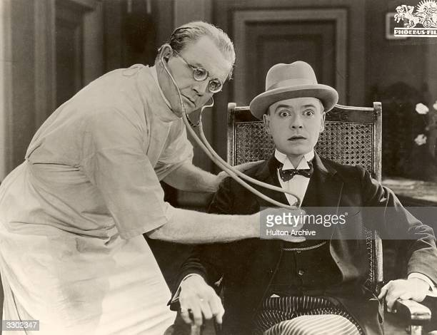 A doctor listens to the rhythm of a patient's heart in a scene from the German silent film 'Komodie des Herzens' directed by Rochus Gliese