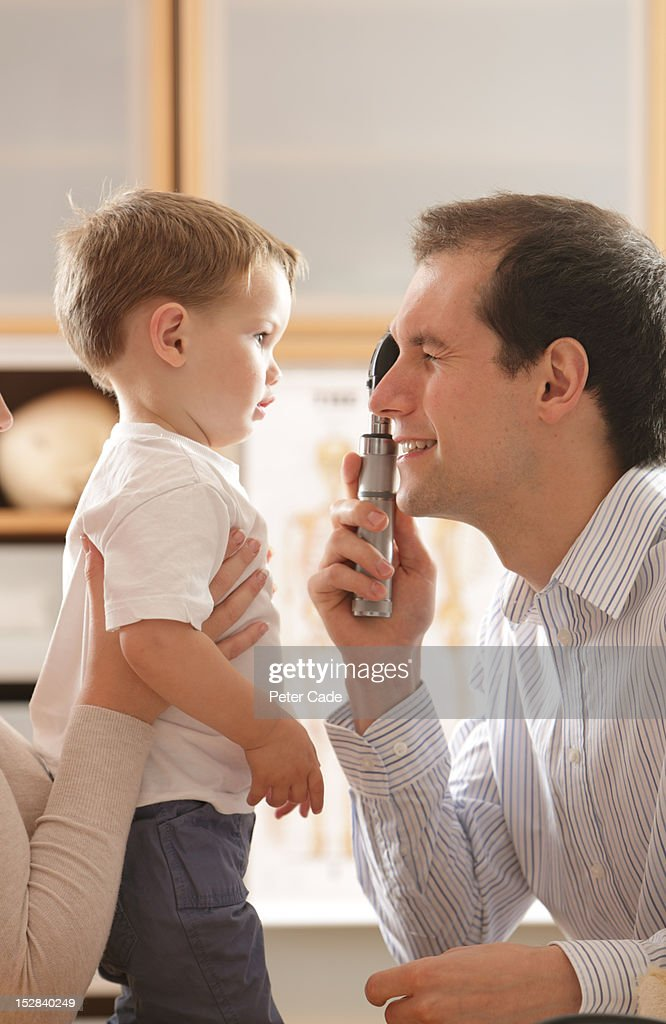 Doctor looking a young boy with opthalmascope : Stock Photo