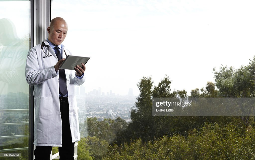 Doctor looking at a digital tablet. : Stock Photo