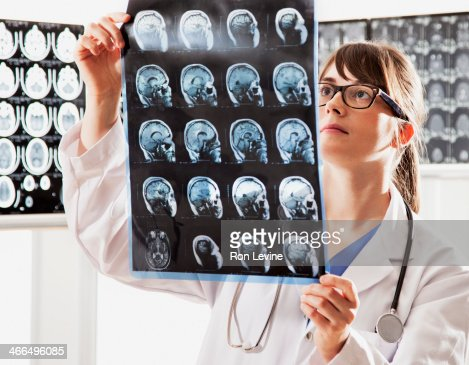 Doctor looking at mri x-rays in clinic : Stock Photo