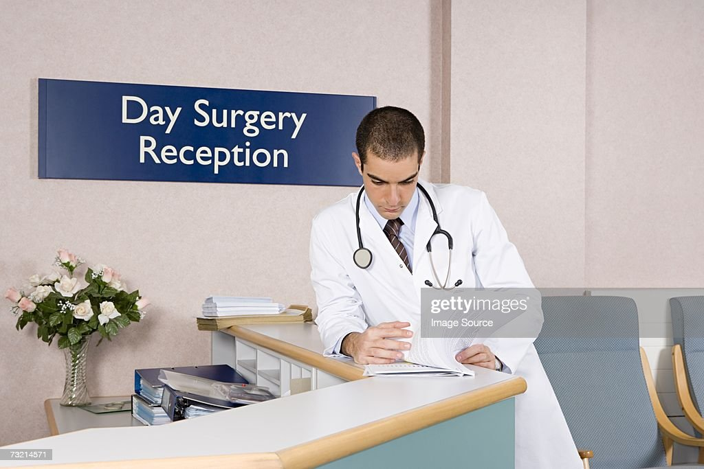 Doctor looking at paperwork : Stock Photo