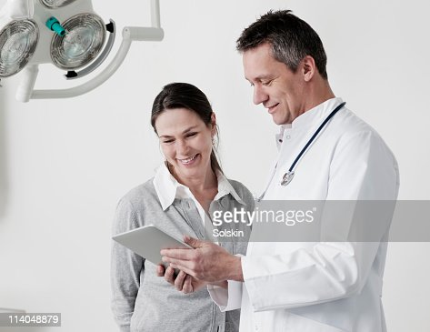 Doctor looking at tablet computer with patient : Stock Photo