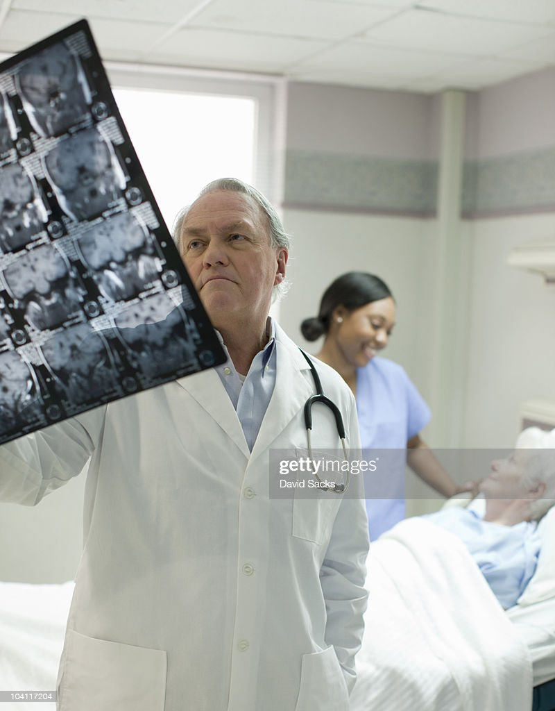 Doctor looking at x-ray with patient in background : Stock Photo