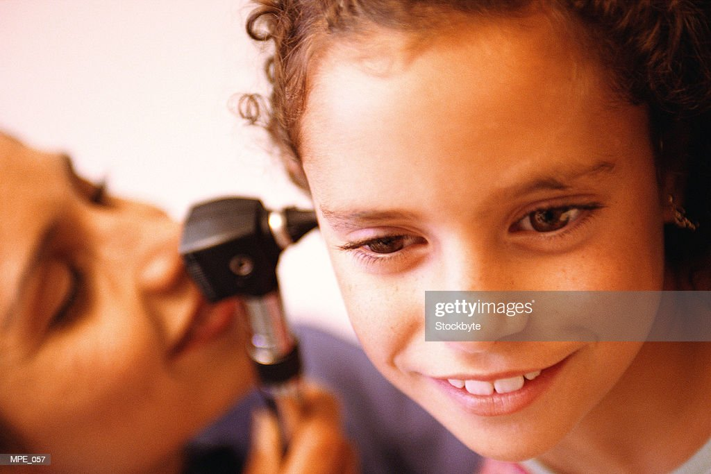 Doctor looking in girl's ear : Stock Photo