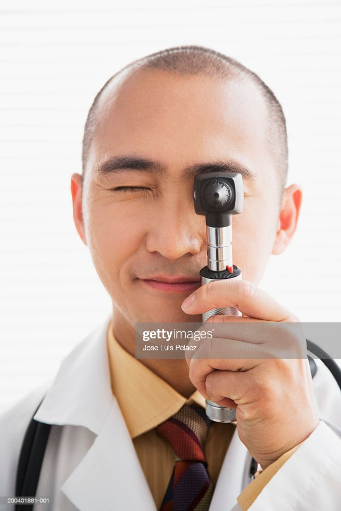Doctor looking through a otoscope