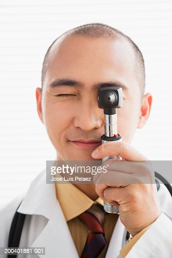 Doctor looking through a otoscope : Stock Photo