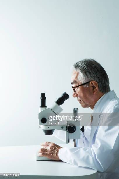 Doctor looking through object using microscope