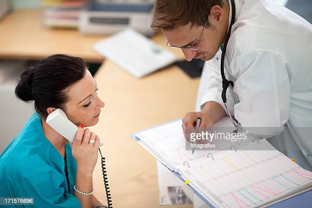 doctor looks into organizer while nurse is at the phone