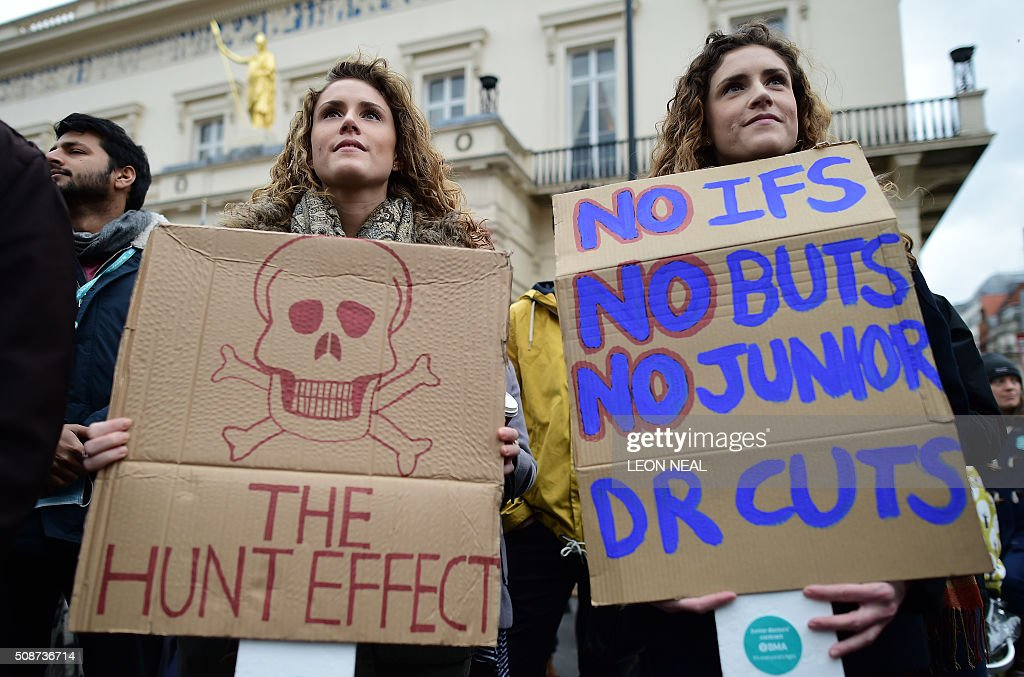Doctor Lucia Stevenson (L) and her twin sister Jacinta Stevenson hold placardsa as they participate in a protest in central London on February 6, 2016, against the British governments' plans to change contracts for junior doctors. Many doctors also claim that Prime Minister David Cameron's government is not providing enough resources for the widely cherished, state-run National Health Service (NHS), founded by a socialist government in 1948 to provide free care. / AFP / LEON NEAL