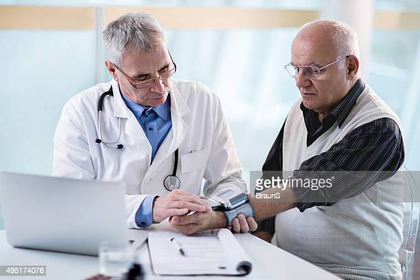 Doctor measuring blood pressure of a senior patient.