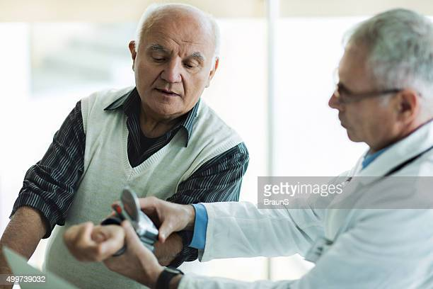Médico medir a pressão arterial do paciente idoso.