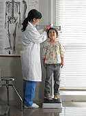 Doctor measuring girl (5-7 years) in examination room
