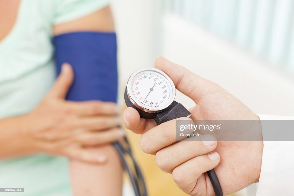 Doctor measuring patient blood pressure : Stock Photo