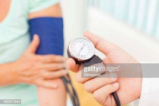 Doctor measuring patient blood pressure : Foto stock