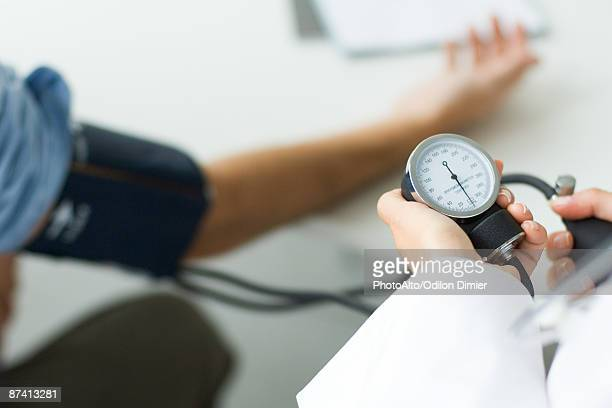 Doctor measuring patient's blood pressure, cropped view