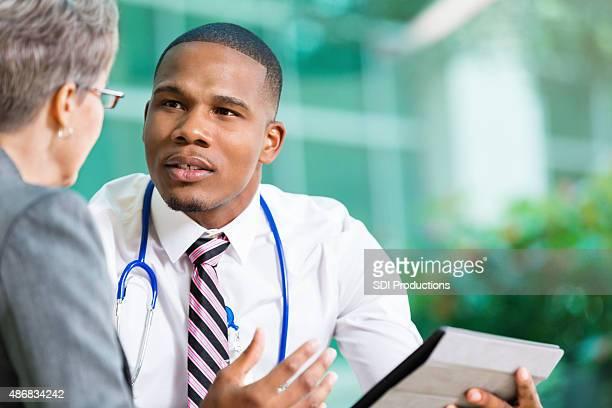 医師ミーティング、上級の患者を使用して、デジタルタブレットを持っている
