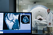 Doctor monitoring patient undergoing MRI scan