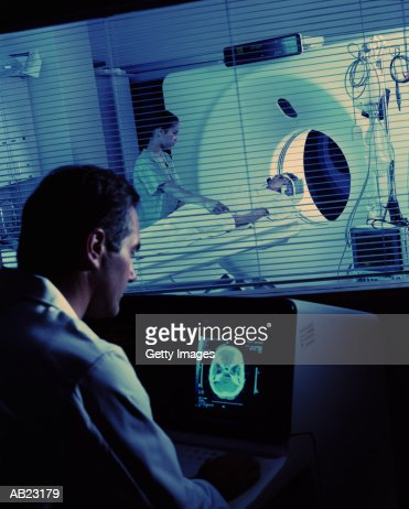Doctor observing medical scan results of female patient : Stock Photo