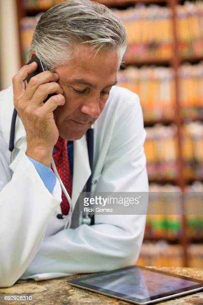 Doctor on the phone in his office while looking at ipad.