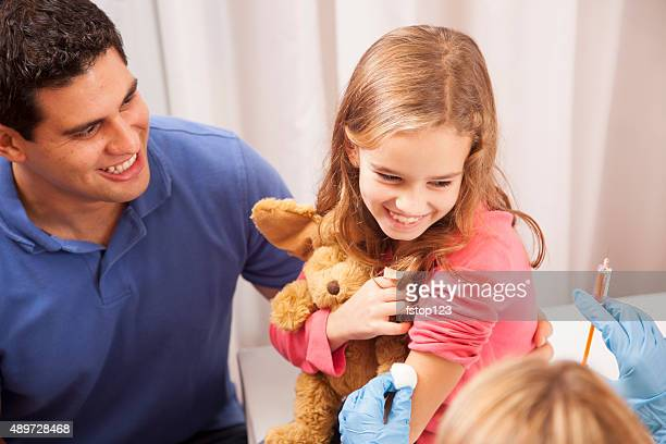 Doctor or nurse gives vaccine to girl patient. Office. Father.