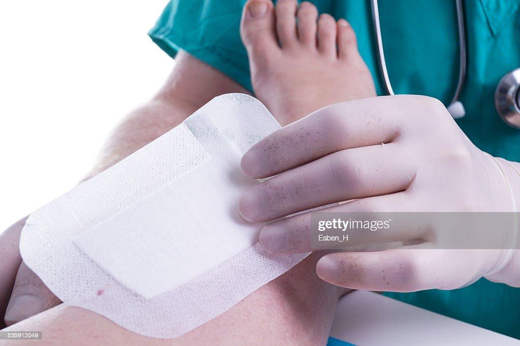 Médico parches una lesión : Foto de stock