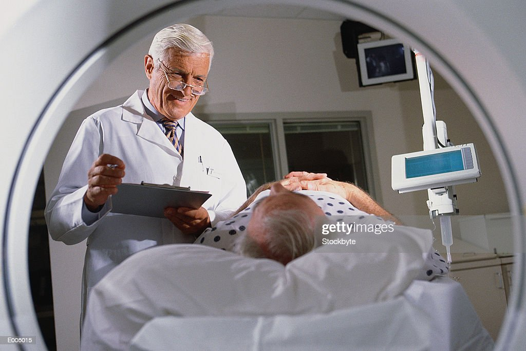 Doctor & patient seen from CAT scan machine : Stock Photo