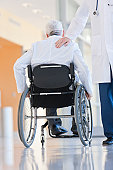 Doctor patting another on the back while in wheelchair with muscular dystrophy