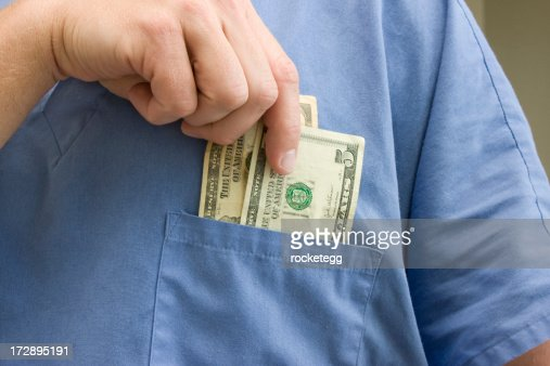 Doctor placing money in his pocket