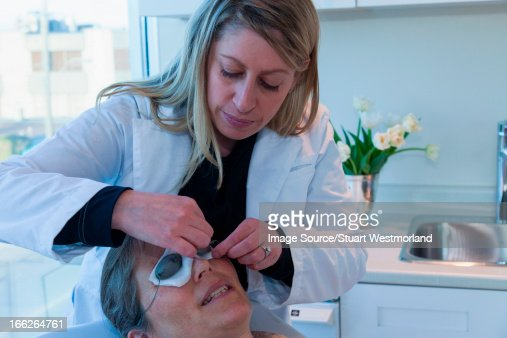 Doctor placing patches on patient's eyes : Stock Photo