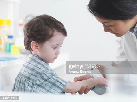 Doctor preparing boy for shot : Stock Photo