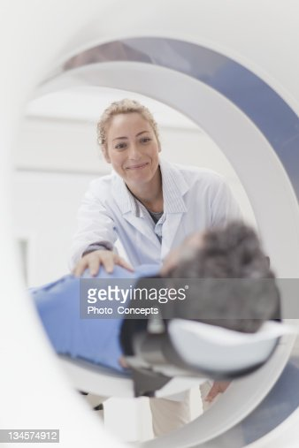 Doctor preparing patient for CT scanner