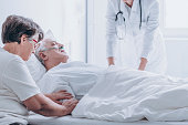 Doctor pronouncing death of an elderly patient in a presence of his spouse