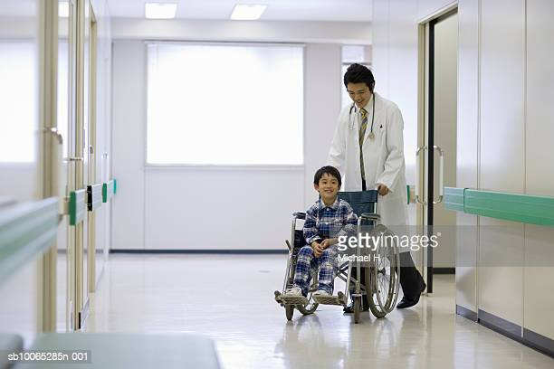 Doctor pushing boy (5-6) in wheelchair in hospital corridor