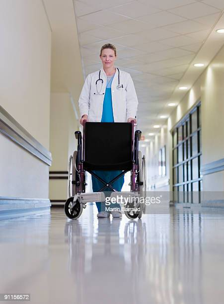 Doctor pushing empty wheelchair