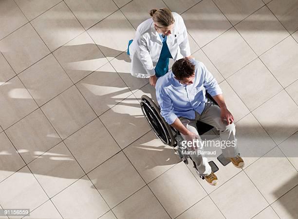 Doctor Mann im Rollstuhl Schieben