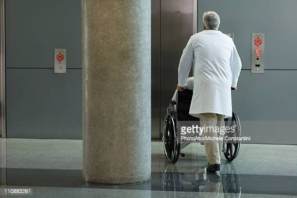 Doctor pushing patient in wheelchair toward elevator