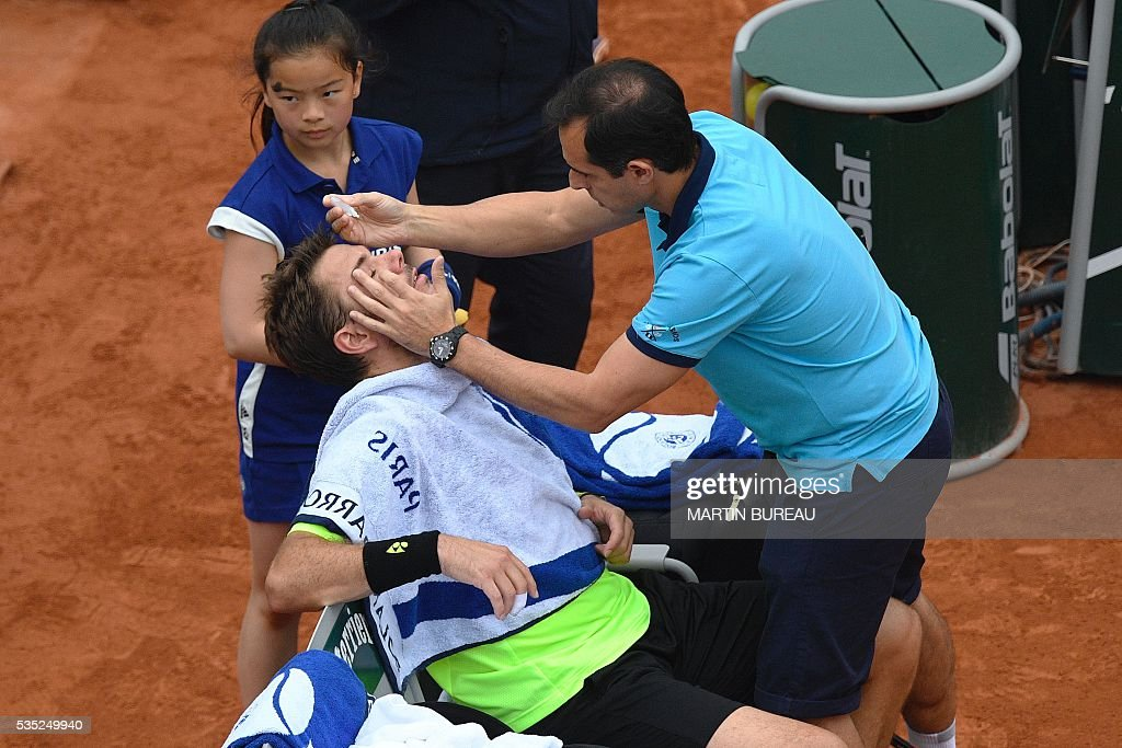 A doctor puts eye drops into the eyes of Switzerland's Stanislas Wawrinka during his men's fourth round match against Serbia's Viktor Troicki at the Roland Garros 2016 French Tennis Open in Paris on May 29, 2016. / AFP / MARTIN