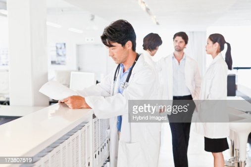 Doctor reading his notes in hallway : Stock Photo