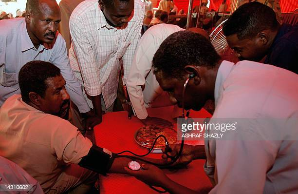 A doctor reads a man's blood pressure on April 19 2012 at a temporary blood clinic that opened at the Presidential Palace in Khartoum to donate blood...