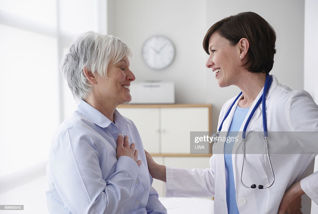 Doctor Reassuring Patient, In Examination Room : Stock Photo