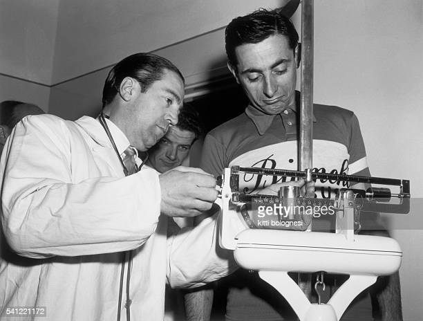 A doctor records the weight of champion cyclist Fausto Coppi